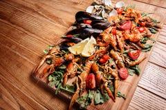 Mexilhões frescos, lagostas, camarão em uma placa de madeira Imagens de Stock Royalty Free