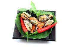 Mexilhões no prato preto e vegetais no prato também. Imagens de Stock Royalty Free