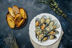 Mexilhões verdes cozidos com o pão torrado do Parmesão e do alho em um branco imagens de stock royalty free