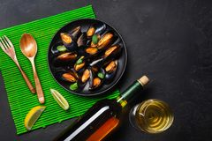 Mexilh?es do marisco, folhas da manjeric?o em uma placa preta com bootle do vinho, copo de vinho, lim?o, colher de madeira e forq imagens de stock