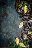Mexilhões pretos frescos na bacia de madeira com limão e ingredientes para cozinhar no fundo rústico escuro, vista superior, bord Fotografia de Stock Royalty Free