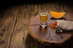 Mezcal - bebida mexicana tradicional con las rebanadas, la pimienta de chile y la sal anaranjadas del gusano en una tabla de made Imagenes de archivo