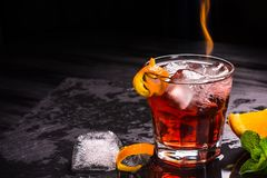 Mezcal Negroni cocktail with flames. Smoky Italian aperitivo. Orange peel. stock image
