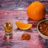 Mezcal schoss mexikanisches Getränk mit orange Scheiben, Paprikapfeffer und Wurmsalz in Oaxaca Mexiko alte schäbige mehrfarbige T Lizenzfreie Stockfotografie