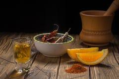 Mezcal tiró la bebida mexicana con la sal anaranjada de las rebanadas, del chile y del gusano en Oaxaca México Foto de archivo libre de regalías