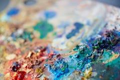Mezcla colorida de la pintura en la paleta de los artistas Imagen de archivo