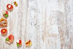 Mezcla de aperitivos/de bocados/de tapas en una tabla de madera Fotos de archivo