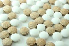 Mezcla de Brown y de píldoras blancas aislados en blanco Imágenes de archivo libres de regalías