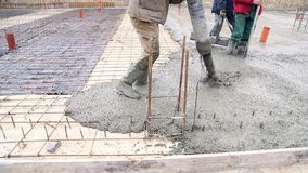 Mezcla de hormigón de colada del mezclador de cemento en encofrado concreting Un grupo de trabajadores que vierten el hormigón en almacen de metraje de vídeo