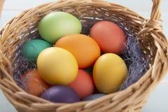 Mezcla de huevos de Pascua brillantes teñidos en a con la cesta con el sisal azul colorido imagen de archivo libre de regalías