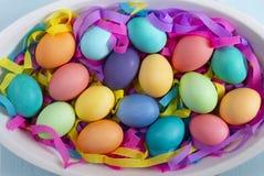 Mezcla de huevos de Pascua brillantes teñidos en un plato con las cintas de papel coloridas imágenes de archivo libres de regalías
