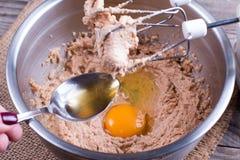 Mezcla de mezcla de la torta del mollete para cocer Añada los huevos y el alcohol Fotos de archivo libres de regalías