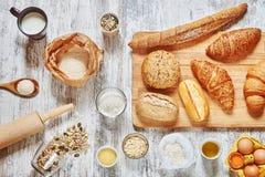 Mezcla de pan fresco y de ingredientes en una tabla de madera Foto de archivo libre de regalías