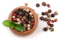 Mezcla de pimienta de las pimientas calientes, roja, negra, blanca y verde en un cuenco de madera aislado en el fondo blanco Visi Imagen de archivo libre de regalías
