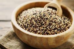 Mezcla de quinoa roja, blanca y negra cruda en la tabla de madera del thw Imagen de archivo