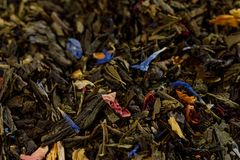 Mezcla de té negro con las flores verdes del té y del aciano del sencha y las rebanadas de la fresa Fondo seco de la textura de l imagen de archivo