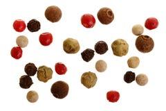 Mezclado de la pimienta caliente, roja, negra, blanca y verde de las pimientas aislada en el fondo blanco Visión superior foto de archivo libre de regalías