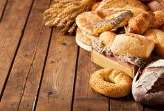 Mezclado del pan cocido fresco con los oídos del trigo Fotografía de archivo libre de regalías