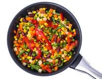 Mezclado vegetal con las habas y el maíz en el sartén, visión superior, aislada en blanco foto de archivo