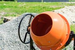 Mezclador concreto de la foto instalado en el emplazamiento de la obra al lado de una pila de arena y de grava fotos de archivo libres de regalías