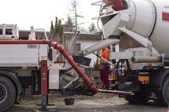 Mezclador de cemento en el hormigón de transferencia a una bomba concreta móvil fotografía de archivo