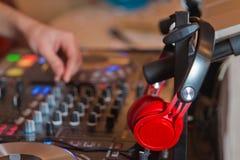 Mezclador de DJ con los auriculares en el club nocturno DJ mezcla la pista en el club nocturno en el partido DJ equipo de sonido  fotos de archivo