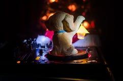 Mezclador de DJ con los auriculares en fondo oscuro del club nocturno con Noche Vieja el árbol de navidad Ciérrese encima de vist Fotos de archivo libres de regalías