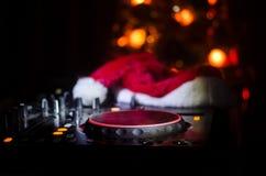 Mezclador de DJ con los auriculares en fondo oscuro del club nocturno con Noche Vieja el árbol de navidad Ciérrese encima de vist Fotografía de archivo libre de regalías