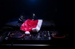 Mezclador de DJ con los auriculares en fondo oscuro del club nocturno con Noche Vieja el árbol de navidad Ciérrese encima de vist Fotografía de archivo