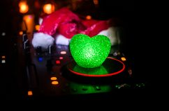 Mezclador de DJ con los auriculares en fondo oscuro del club nocturno con Noche Vieja el árbol de navidad Ciérrese encima de vist Imagenes de archivo