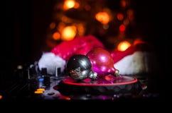 Mezclador de DJ con los auriculares en fondo oscuro del club nocturno con Noche Vieja el árbol de navidad Ciérrese encima de vist Imagen de archivo libre de regalías