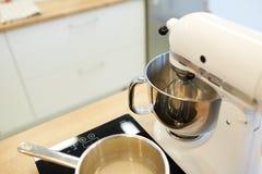Mezclador eléctrico y pote en estufa en la cocina Fotos de archivo libres de regalías