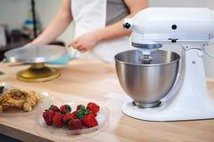 Mezclador en la tabla de cocina con las frutas en un fondo blanco, cocinando la crema imagen de archivo libre de regalías