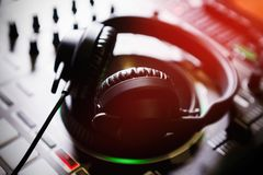 Mezclador y auriculares profesionales de los sonidos de DJ con música imagen de archivo
