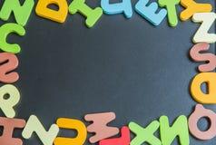 Mezcle la palabra de madera colorida del alfabeto en tablero negro Fotografía de archivo