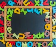 Mezcle la palabra de madera colorida del alfabeto en tablero negro Imagen de archivo