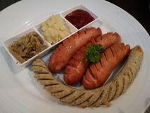 Mezcle la salchicha, Bratwurst y la salchicha alemanes del humo, con el puré de patata y la chucrut para sumergir con la salsa de Imágenes de archivo libres de regalías