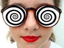 Mezmerized by Dreamstime. A girl wearing glasses with hypnotic spirals like the dreamstime logo Royalty Free Stock Image