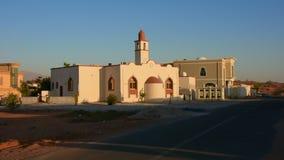 Mezquita blanca en un área residencial en el Medio Oriente con un cielo azul a finales de la sol de la tarde almacen de video