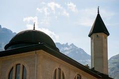 Mezquita islámica en el fondo de montañas y del cielo nevosos Imagen de archivo