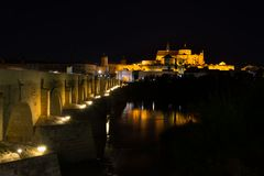 Mezquita and Roman bridge in Cordoba by night. Andalusia, Spain stock image