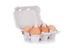Mezza dozzine uova marroni del pollo in casella isolata Fotografie Stock