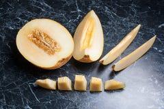 Mezza e frutta affettata del melone di melata su fondo di marmo scuro Fotografia Stock Libera da Diritti