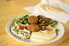 Mezza and Falafel plate. With hummus, baba ganoush(egg plant spread), tabouli salad, and dolmas(stuffed grape leaves Stock Images