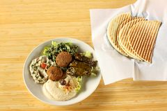 Mezza and Falafel plate. With hummus, baba ganoush(egg plant spread), tabouli salad, and dolmas(stuffed grape leaves Royalty Free Stock Photos