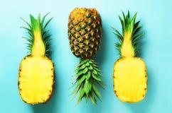 Mezza fetta di ananas fresco e di intera frutta su fondo blu Vista superiore Copi lo spazio Modello luminoso degli ananas per Fotografia Stock