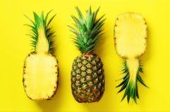 Mezza fetta di ananas fresco e di intera frutta su fondo giallo Vista superiore Copi lo spazio Modello luminoso degli ananas per Immagini Stock