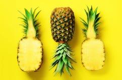 Mezza fetta di ananas fresco e di intera frutta su fondo giallo Vista superiore Copi lo spazio Modello luminoso degli ananas per Fotografia Stock Libera da Diritti