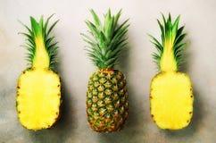 Mezza fetta di ananas fresco e di intera frutta su fondo grigio Vista superiore Copi lo spazio Modello luminoso degli ananas per Fotografia Stock