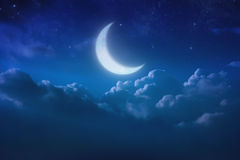 Mezza luna blu dietro nuvoloso sul cielo e sulla stella alla notte all'aperto Immagine Stock